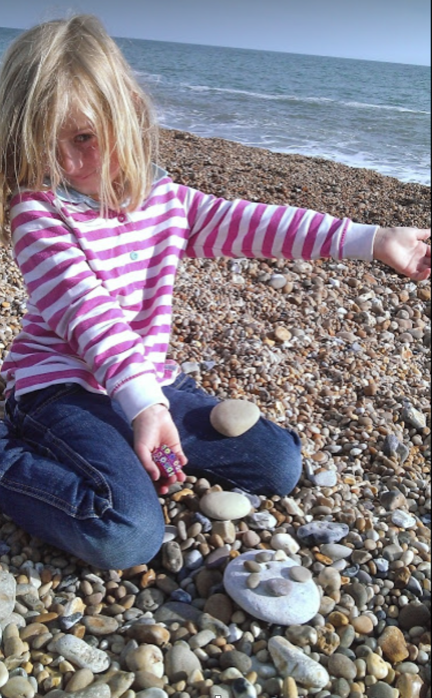 small girl on a pebble beach